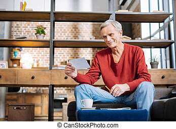 Positive elderly man holding a note