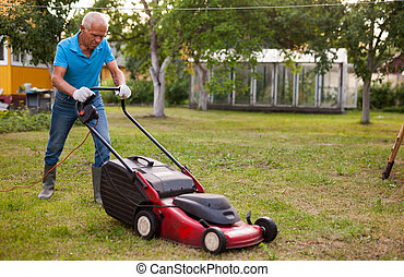 Positive elderly man with lawnmower when mowing the lawn
