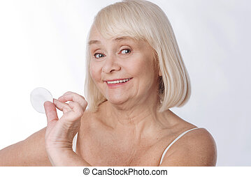 Positive elderly woman caring about her appearance