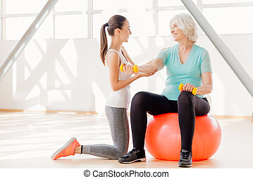 Positive elderly woman exercising with dumbbells