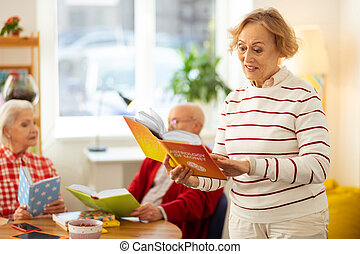 Positive elderly woman reading a book about astrology
