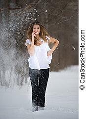 Positive emotion. Fashion model posing in snowdrift in wood