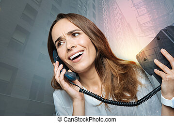 Positive emotional woman talking on the phone