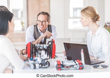 Positive engineers creating robot in office