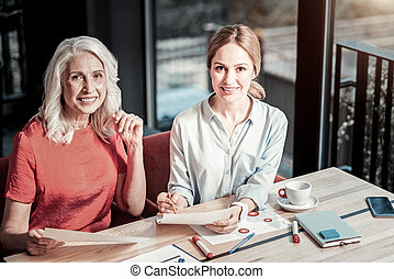 Positive experienced designers smiling cheerfully while working together