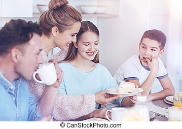 Positive family enjoying breakfast together