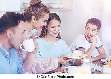 Positive family enjoying breakfast together