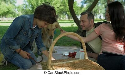 Positive family enjoying picnic with their dog