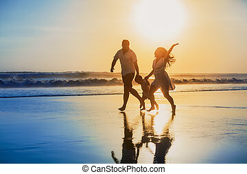 Positive family running with fun on the sunset beach - Happy...