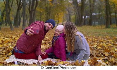Positive family taking selfie on cellphone in autumn -...