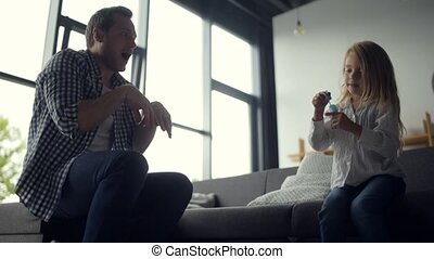 Positive father and cute daughter blowing soap bubbles -...