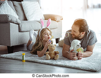 Cheerful girl is blowing soap bubbles with enjoyment. She is lying on rug near teddy bear while wearing cute rabbit ears. Her daddy is looking at child with fondness