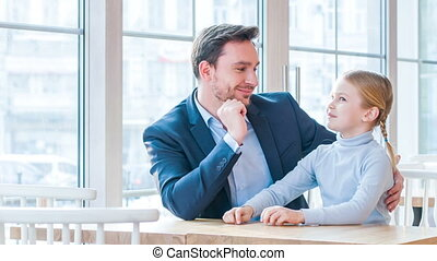 Positive father and his little daughter sitting in the cafe