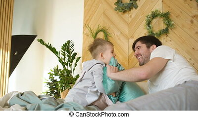 Positive father and son having fun and fight piloows on bed at home