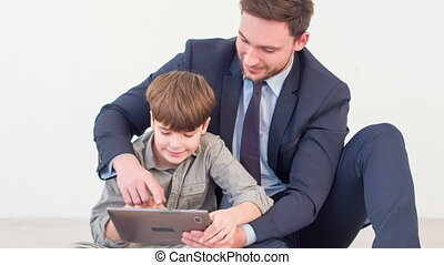 Positive father and son using tablet