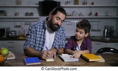 Positive father giving housework tasks to his son - Positive...