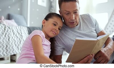 Positive father reading for his little daughter