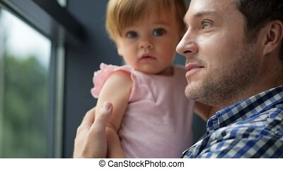 Positive father standing near window with his cute daughter in hands