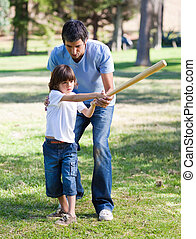 Positive father teaching baseball to his son