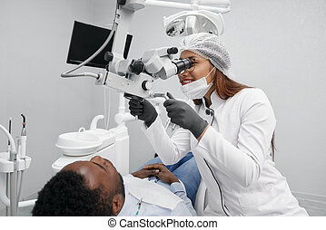 Positive female dentist curing teeth of male patient