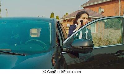 Positive female driver speaking on phone near car