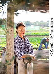 Positive female gardener posing in backyard garden
