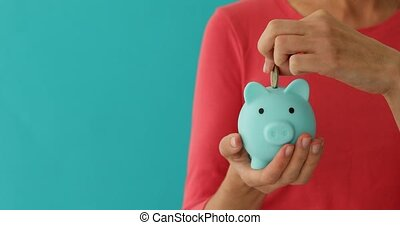 Positive female putting coin in piggybank, planning budget,...
