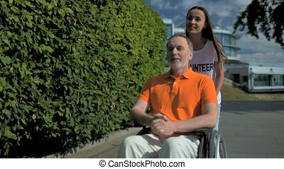 Positive female volunteer pushing a wheelchaired man