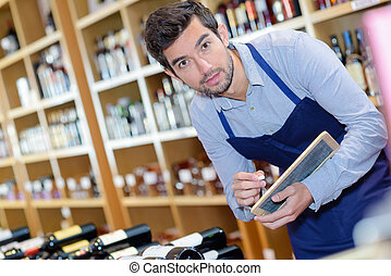 positive friendly man seller wearing apron in wine house