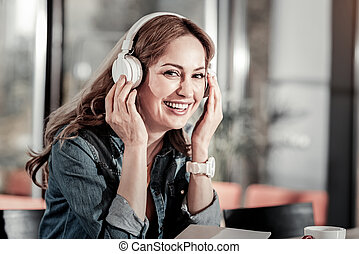 Positive friendly woman smiling and listening to a new song