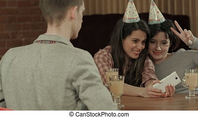 Positive friends having fun at party posing to take a selfie with smartphone