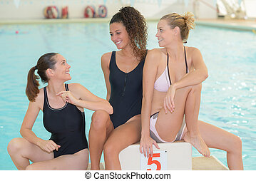 positive friends swimming in a pool