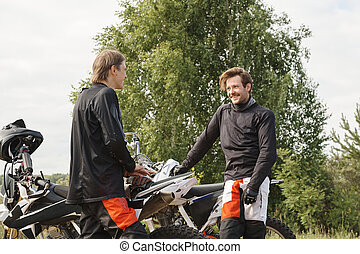 Positive friends talking about motorcycling