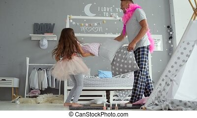 Positive girl and her father fighting with pillows
