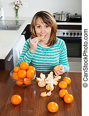 girl eating mandarin in  kitchen