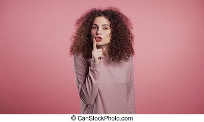 Positive girl holding finger on her lips over pink ...
