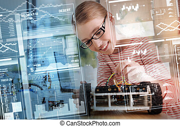 Positive girl in glasses smiling while fixing wires in her new robot