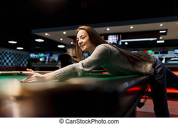 Positive girl plays billiards at leisure