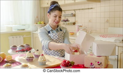 Positive girl putting cake in the b