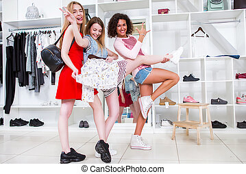 Positive girlfriends hanging out together in a stylish fashion shop fooling around showing rock-n-roll signs holding one friend s leg
