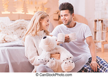 Positive good looking couple holding tea cups