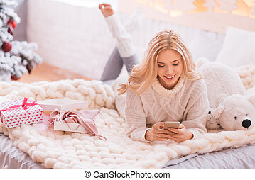 Positive good looking woman using cell phone