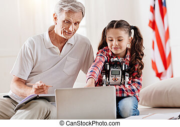 Positive grandfather helping his granddaughter with homework