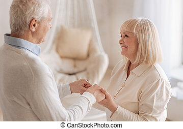 Positive grey haired woman looking at her husband