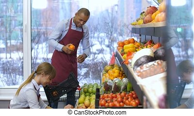 Positive grocery store owners working at store - Positive...