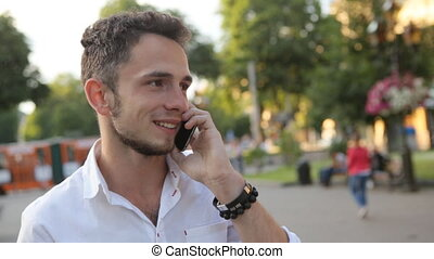 . Positive guy lively speaks on cellphone outdoors and...