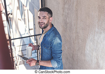 Positive guy with stubble is resting outdoors