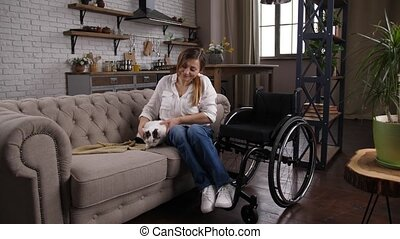 Caring woman with impaired mobility taking pet on knees and gently stroking while sitting on sofa during break in work at home. Cheerful disabled female relaxing with cat in comfortable domestic room