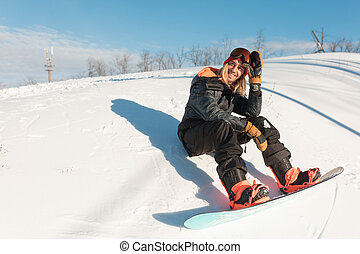 positive handsome guy taking a break after snowboarding