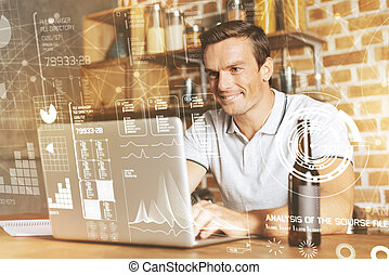Positive handsome man programming at home